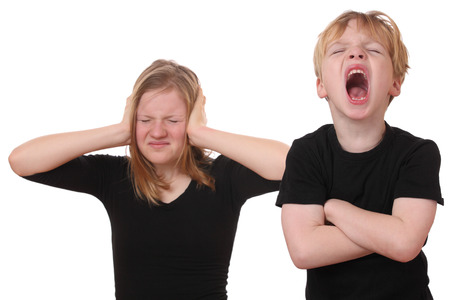 Screaming young boy and girl covering her ears photo