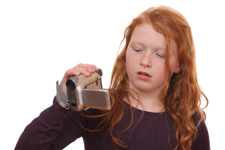 Portrait of a young girl holding a camcorder on white background