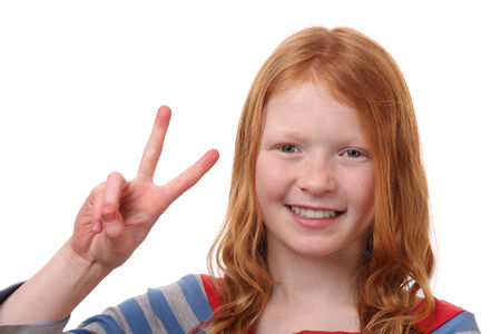 Portrait of a happy young girl showing victory sign on white  photo