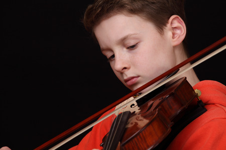 Young boy plays violin on black background photo