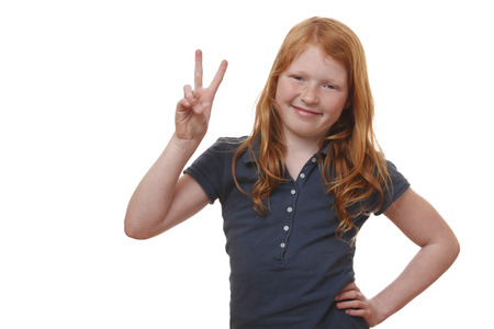 Portrait of a young girl showing victory sign on white background photo