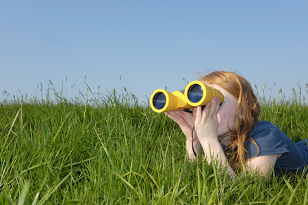 Young girl with binoculars in a meadow searching the sky photo