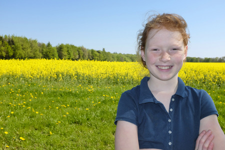 Happy young girl in front of a field of canola photo