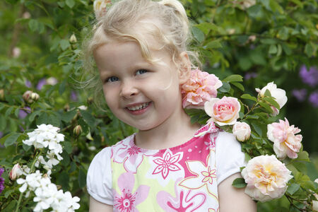 Adorable young girl enjoys some roses in the garden photo