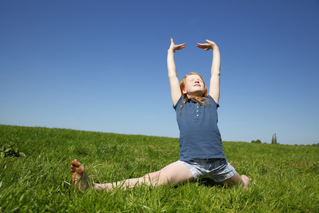 splits: Young girl doing the splits in a green meadow