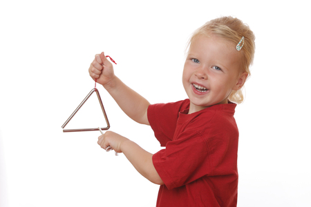 Portrait of a young girl playing a triangle on white background