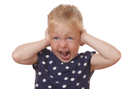 Stressed young girl covers ears with hands on white background