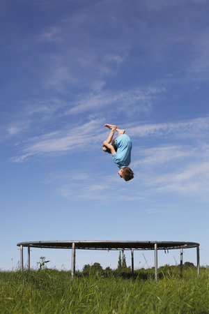 backflip: Young boy doing a backflip on a trampoline on green meadow