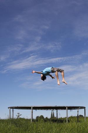 Jeune garçon faisant un backflip sur un trampoline sur le pré vert Banque d'images