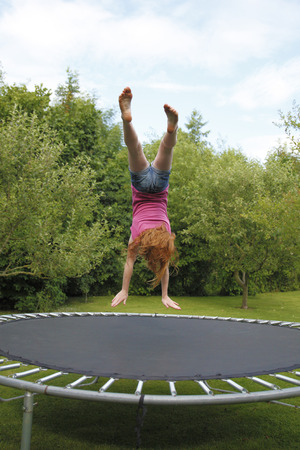 backflip: Young girl jumping on a trampoline in the garden