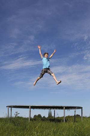 boy gymnast: Young boy jumping on a trampoline on green meadow