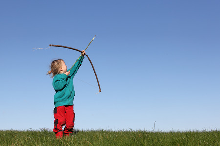 bow and arrow: Young girl outdoors with bow and arrow Stock Photo