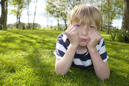 stubborn: Portrait of a stubborn young boy outside in the garden