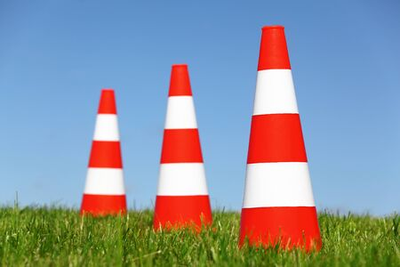 traffic   cones: Three traffic cones on a green meadow Stock Photo