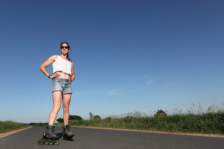 inline skater: Young woman with  on a road Stock Photo