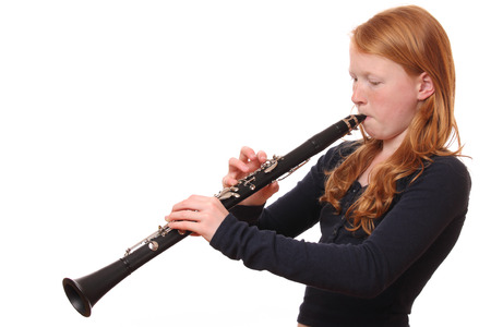 clarinete: Portrait of a teenage girl playing clarinet on white background
