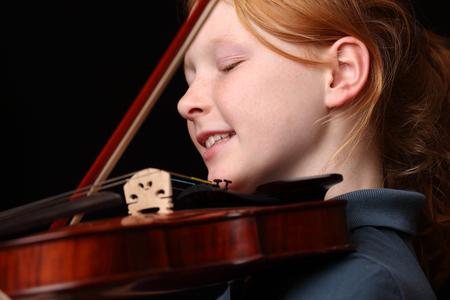 violinista: Retrato de una niña tocando el violín en fondo negro