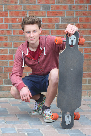 Portrait of a cool young teenage boy outdoors with skateboard Stock Photo