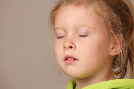 Portrait of a serious child girl with closed eyes on gray background