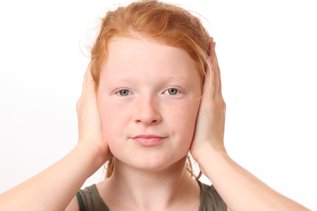 hands covering ears: Portrait of a teenage girl covering ears with hands on white background Stock Photo