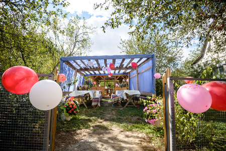Beautiful decorated wooden pavilion with baloons and bouquets roses pastel colors table standing on green grass near trees sunny day, horizontal photo. Stock Photo