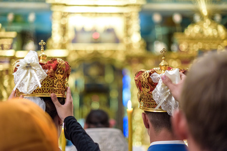 christian marriage: Happy bride groom in crowns at wedding ceremony in church.