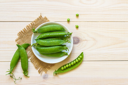 Green pea in bowl of top view on rustic wooden background with copy space, natural wooden table. Flat lay.