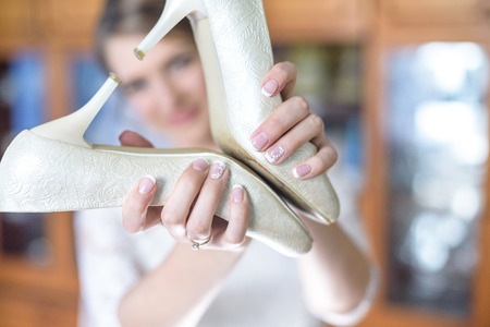 Close up portrait of cute bride girl holding wedding shoes in form of heart in her hand.