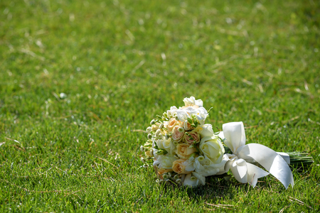 Wedding bouquet of roses on green grass. Stock Photo