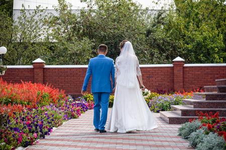 Bride and Groom are walking away in garden