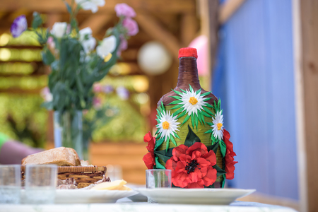 Decorated big bottle of alcohool on wooden table Stock Photo