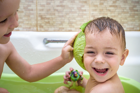 Happy siblings: Two little twins children playing together with water by taking bath in bathtub at home. Kid boys having fun together.