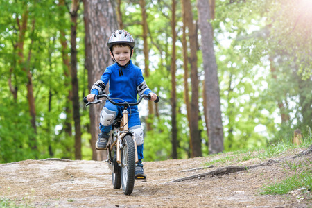 Happy funny little kid boy in colorful raincoat riding his first bike on cold day in forest. Active leisure for children outdoors. Happy carefree childhood concept.