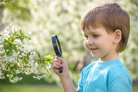 Serious and smiling cute kid guy exploring the environment with a magnifying glass Stock Photo
