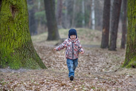 outumn: kid running in the outumn forest. Boy happy running in fallen leaves to his mother.