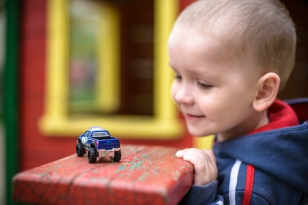 Little toddler boy playing with car toy. Selective focus on car of toddler. Smiling and having fun. Leasure evening play with children concept.