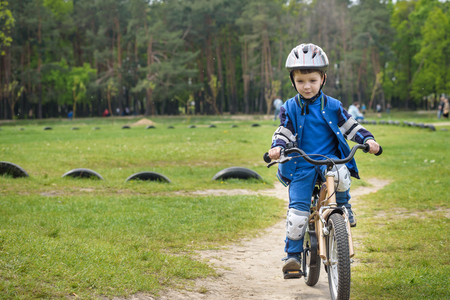 first day: Happy cute blond kid boy having fun his first bike on sunny summer day, outdoors. Happy child making sports. Active leisure for children.Kid boy wear safety helmet. boy is smiling and cicling. Stock Photo