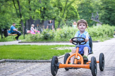 Little preschool boy driving big toy sports car and having fun, outdoors. Active leisure with kids on warm summer day or evening. Stock Photo
