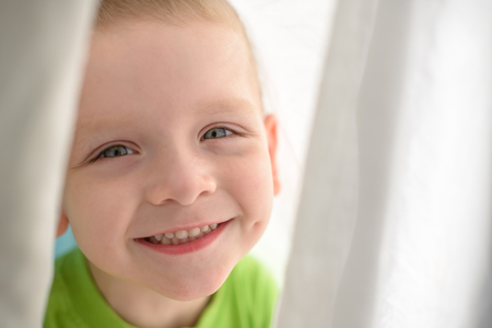 kid face smiling under blanket happy boy looking directly to camera and happy