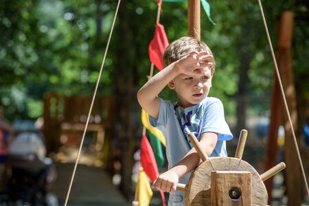 Boy as a captain or sailors play on the ship outdoors on sunny day. Kid has a lot of fun. Ship has colorful flags on wind.