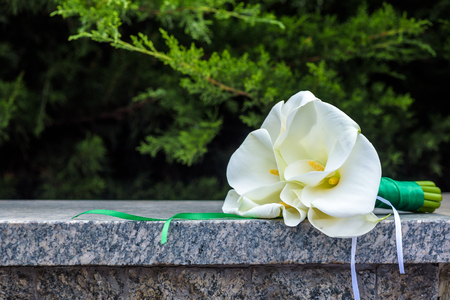 Wedding bouquet of lily on stone with green grass or bush background