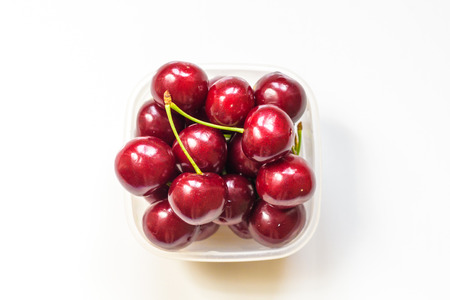 Red Cherries in a glass bowl isolated on white background