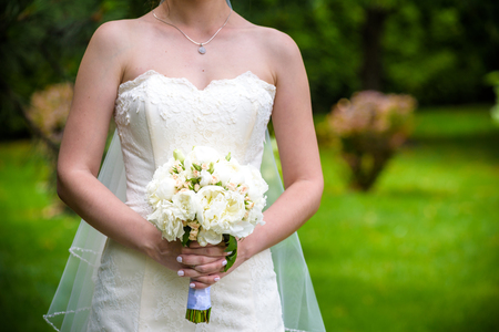 Caucasian bride holding wedding bouquet of various flowers.