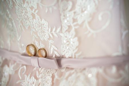 Two wedding rings laying on wedding dress.