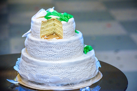 Three-tiered Wedding Cake Is Decorated With Flowers And Stands ...