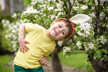 Little boy hunting for easter egg in spring garden on Easter day. Cute little child with traditional bunny celebrating feast. Archivio Fotografico