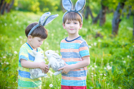 Two little kids boys and friends in Easter bunny ears during traditional egg hunt in spring garden, outdoors. Siblings having fun with finding colorful eggs. play with toy rabbit Stock Photo