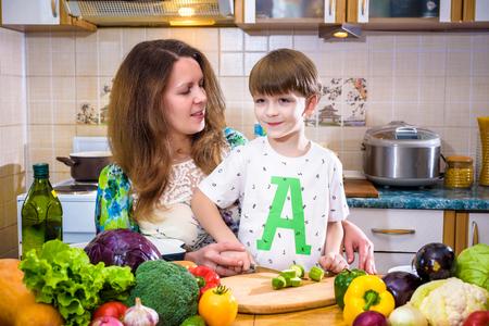 台所で小さな息子と一緒に立って野菜を切る若い料理人の母親。家庭料理のコンセプト 写真素材 - 97430880