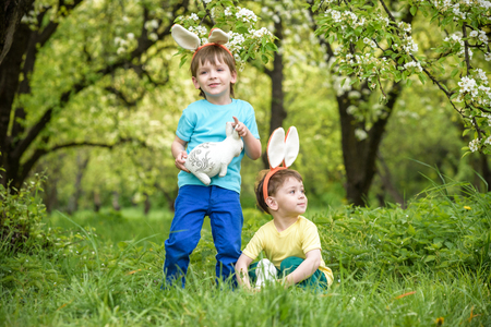 Two little kids boys and friends in Easter bunny ears during traditional egg hunt in spring garden, outdoors.
