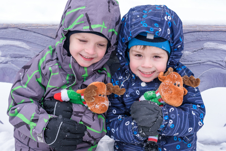 two adorable preschool kids brother boys in winter wear sit amoung snow and play with toy reindeer.